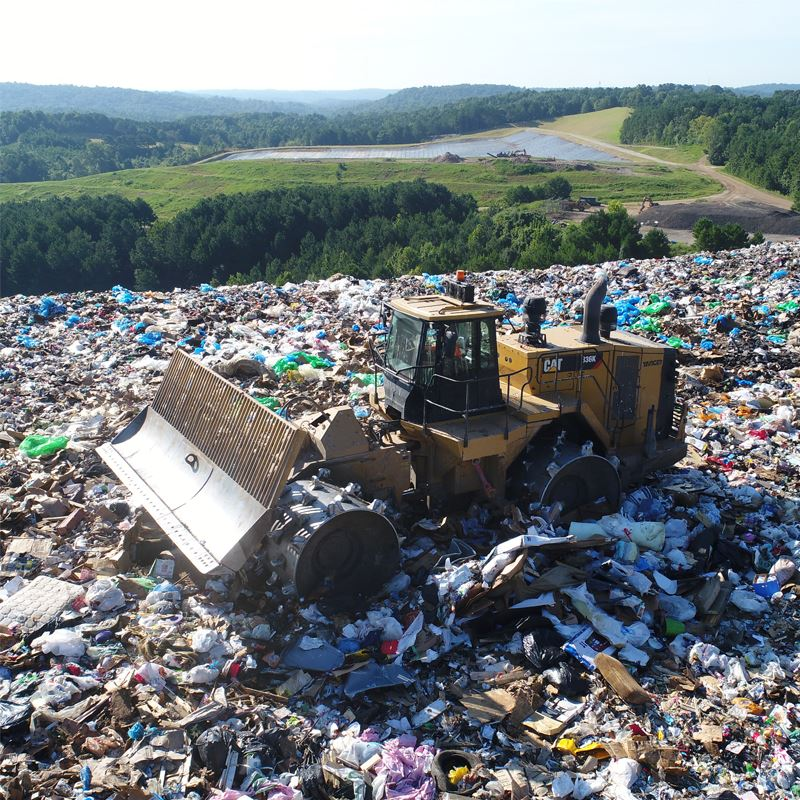 A bulldozer pushes trash on top of the Hall County landfill.
